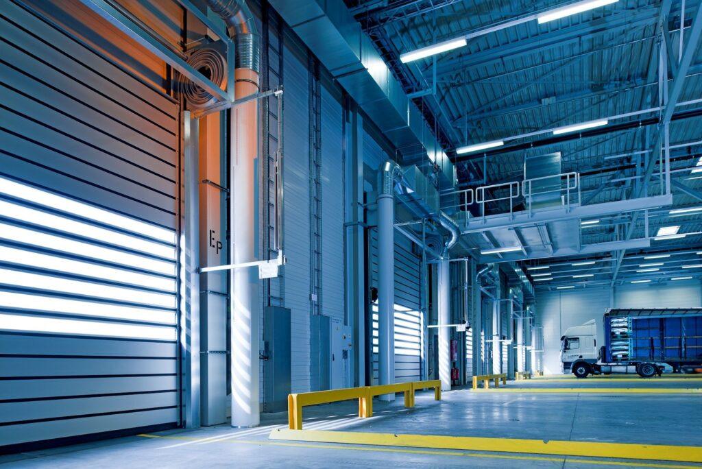 blue warehouse with white garage doors. truck garage.