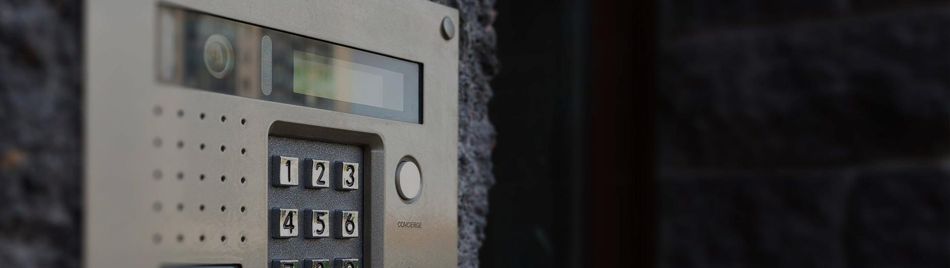 alarm and intercom system on black brick fence