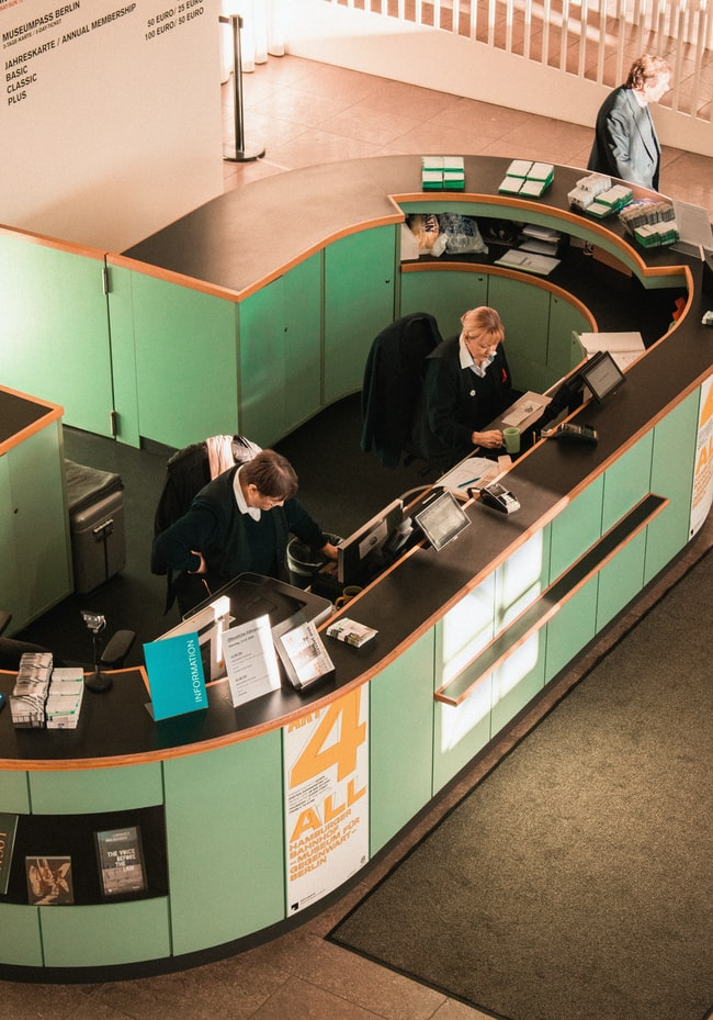 birds eye view of reception desk. two people behind reception. green reception desk.